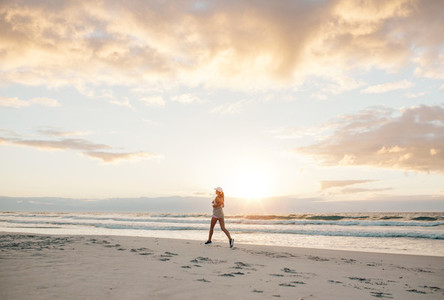 Healthy female jogging on the sea shore