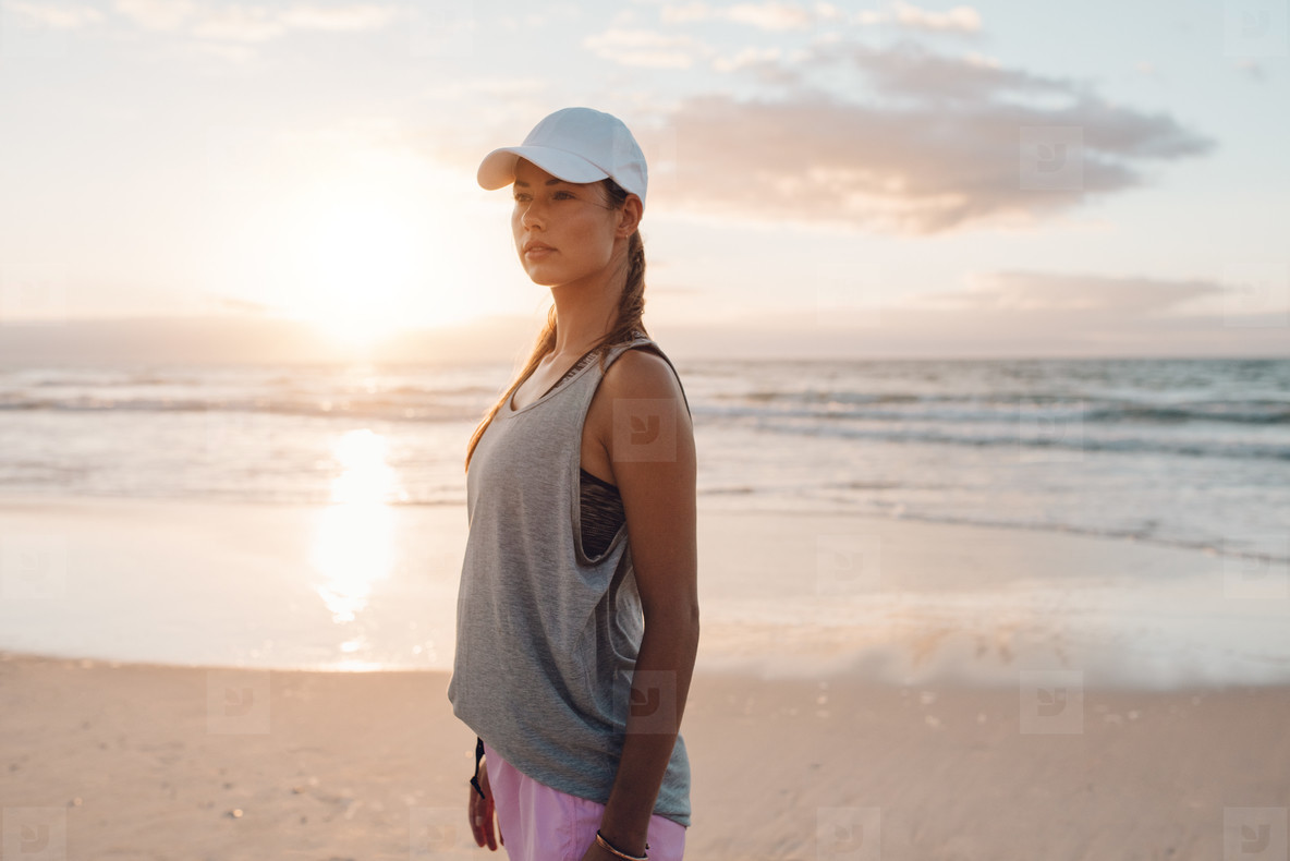 Fit young woman in sportswear standing on the beach