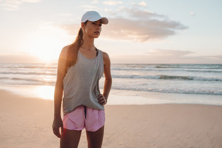 Fitness model in sportswear standing on the beach
