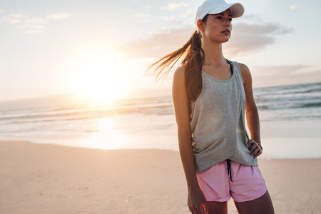 Fit young woman standing on the beach