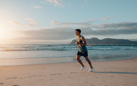Fit young man jogging on the beach
