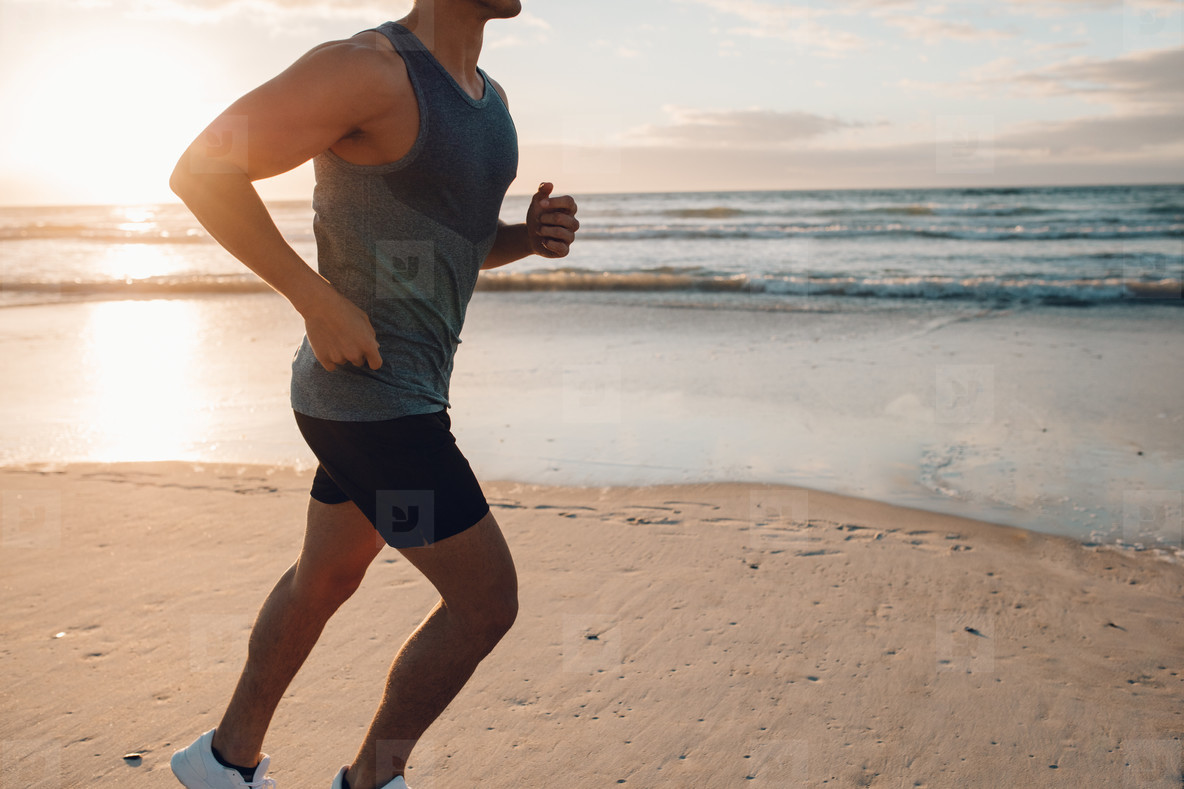 Young man running along the beach in morning