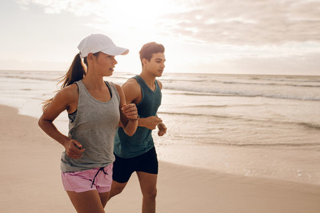 Fitness couple running at beach