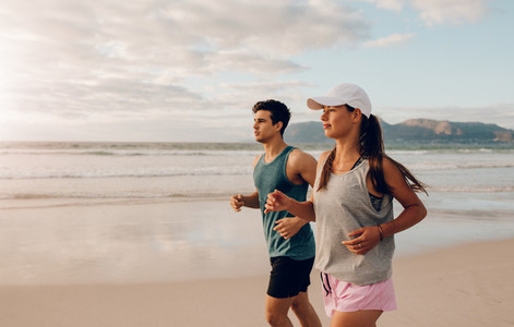 Young man and woman jogging in morning