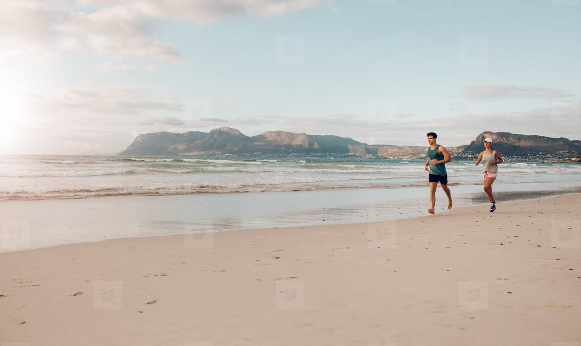 Couple on morning run at the beach