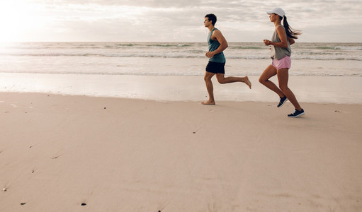 Young couple on running along the shore