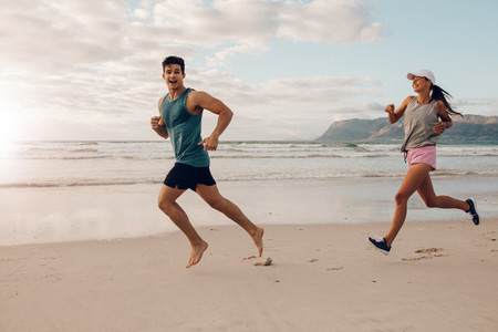 Happy young couple of runners on the beach