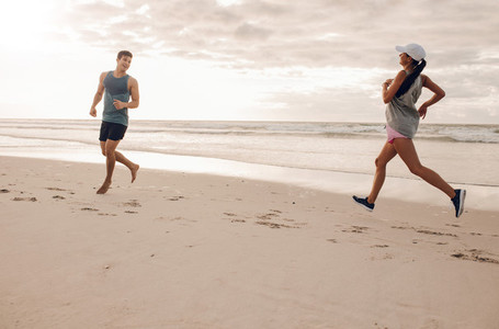 Young man and woman running in morning on beach