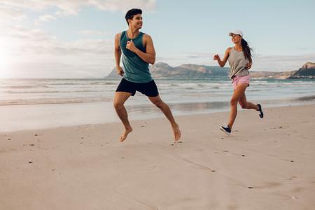 Fitness couple running on the beach