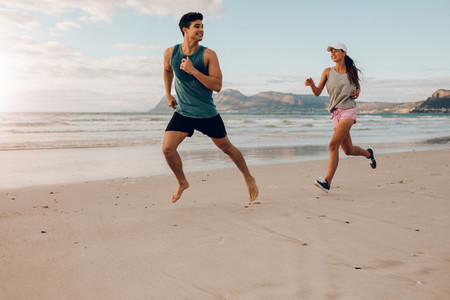 Fitness couple running on the beach