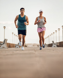 Two young people running on road