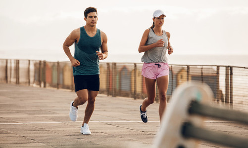 Fitness couple jogging on the sea side promenade