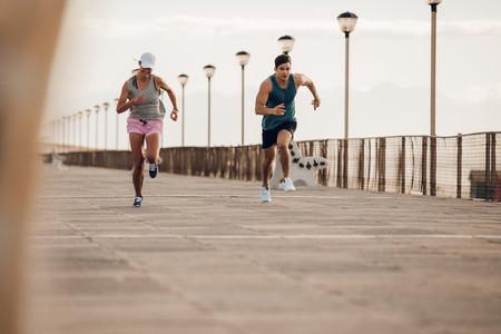 Young couple running along a seaside promenade