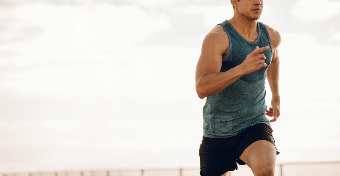 Young man running along a seaside promenade