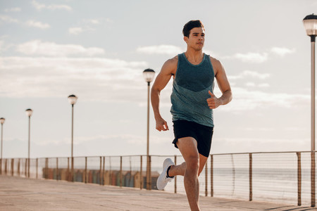 Fit young man running on seaside promenade