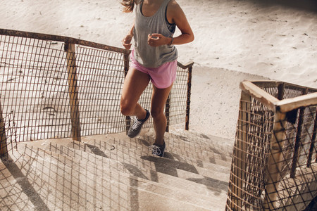 Fit young woman climbing up the steps on beach