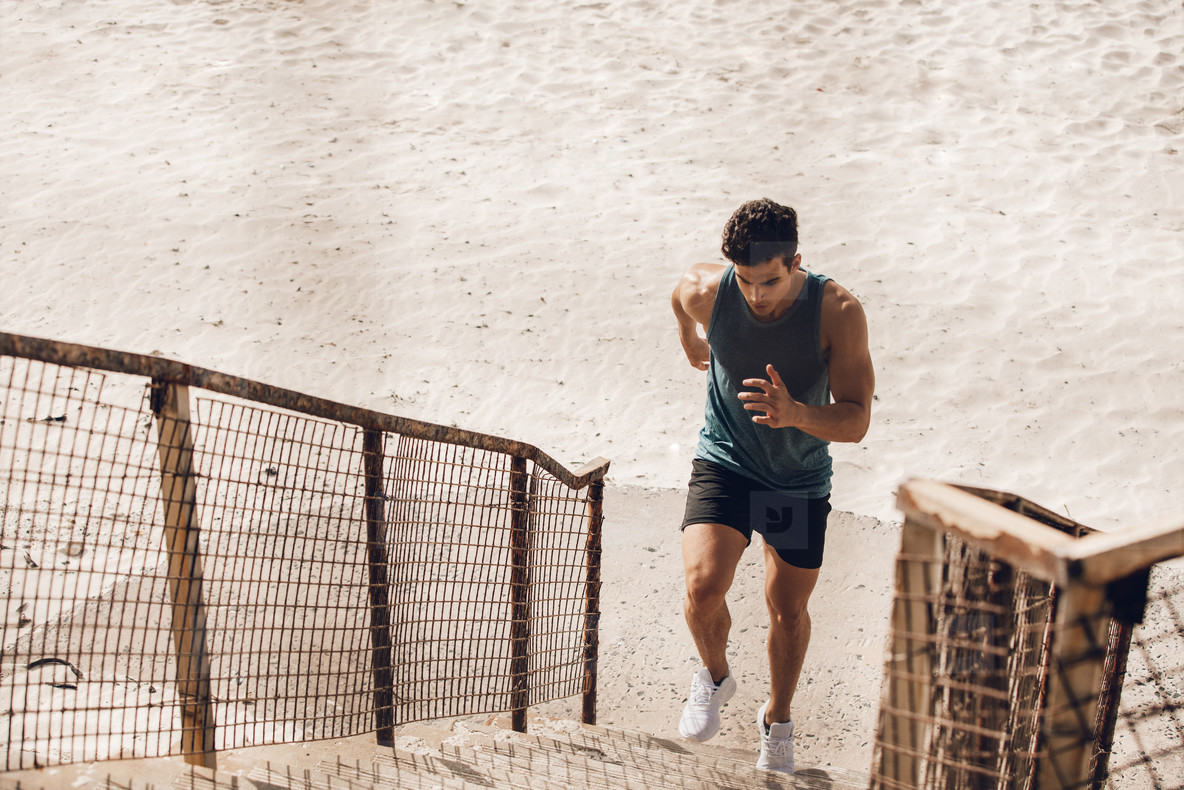 Man running up the staircase on beach