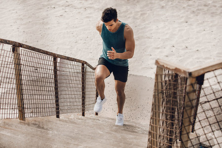 Runner exercising on the staircase on beach