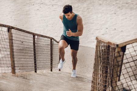 Runner exercising on the staircase on beach