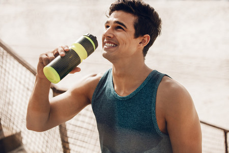 Happy young man drinking water after workout outdoors
