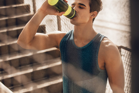 Muscular young man drinking water after workout