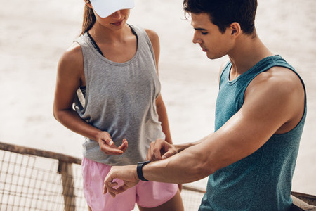 Fitness couple checking performance on a smart watch