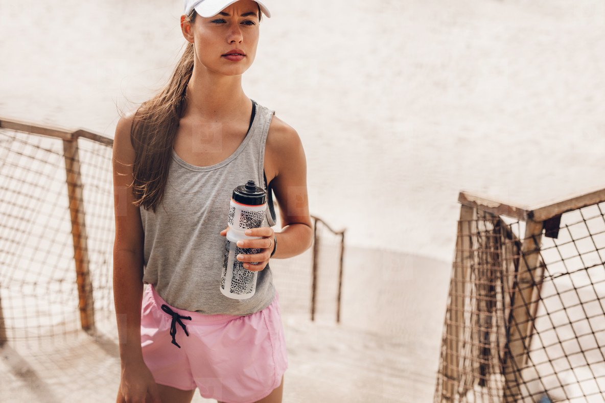 Beautiful runner at the beach with water bottle