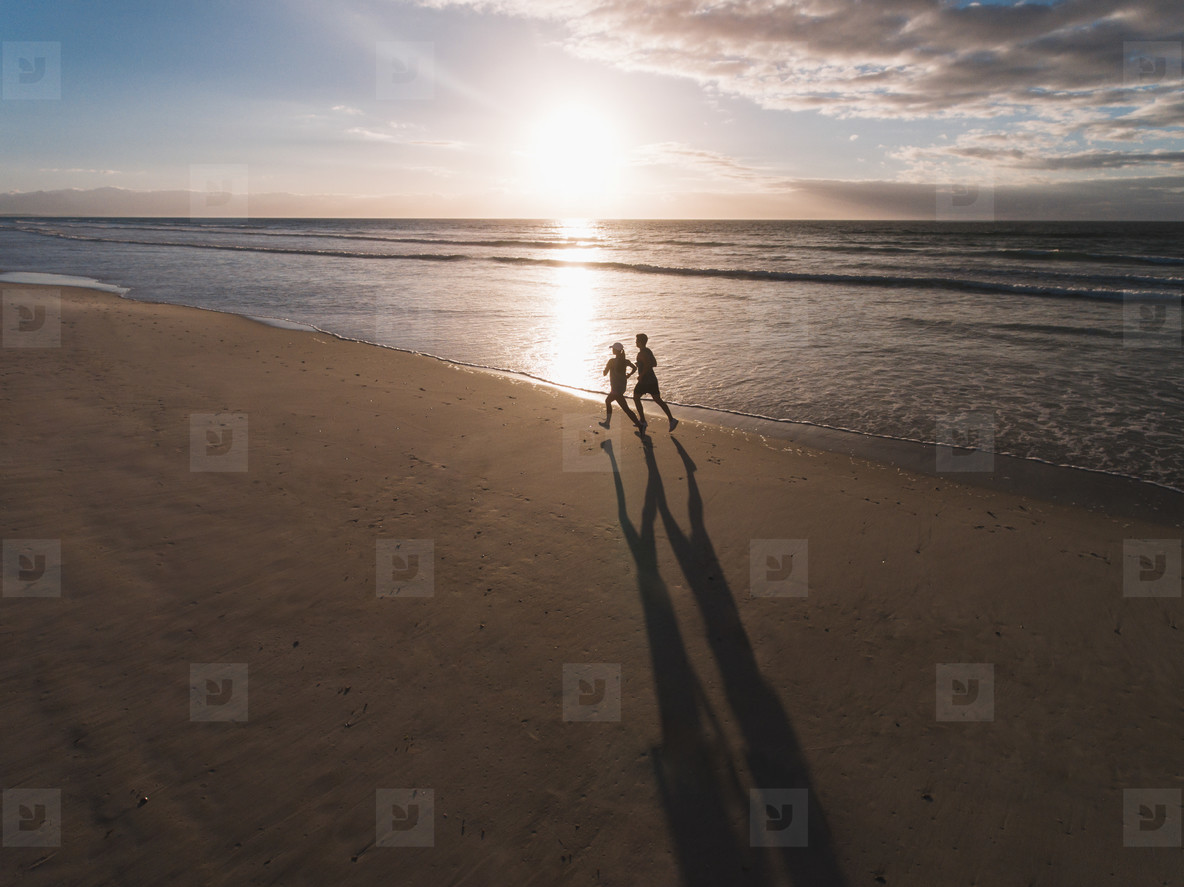 Beautiful beach with couple of runner running on the shore