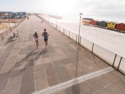 Young couple on morning run at beach promenade