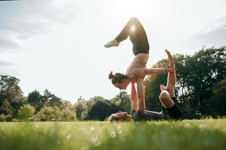 Couple doing acro yoga in pair