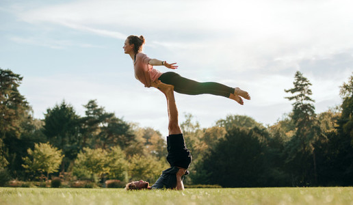 Fit young couple doing acro yoga on park