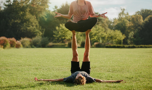 Couple in park practising pair yoga poses