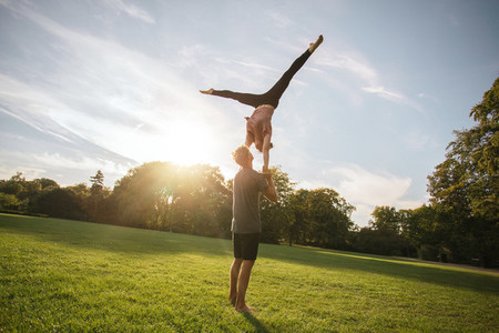 Fit young couple doing acro yoga in park