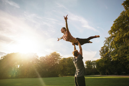 Couple practicing acroyoga at park