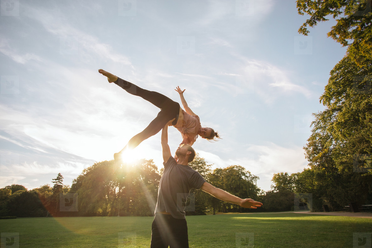 Young couple doing acroyoga at the park
