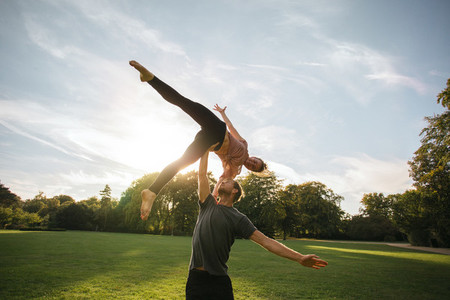 Man and woman doing pair yoga outdoor in a park
