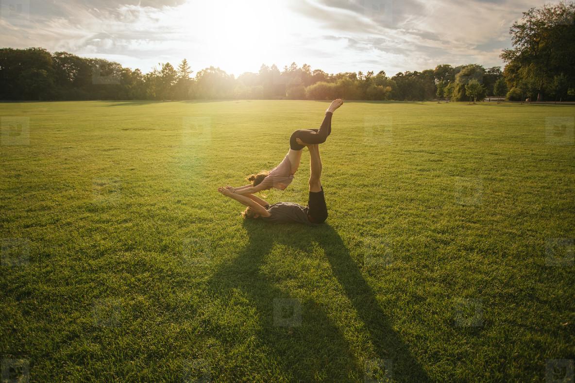 Couple doing acro yoga in lawn