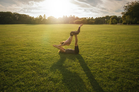 Couple doing acro yoga in lawn