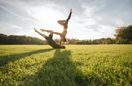 Healthy couple doing acro yoga on grass
