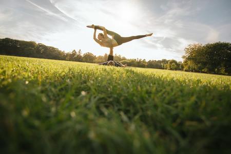 Man and woman in park practising pair yoga
