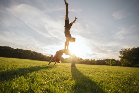 Young man and woman doing yoga in pair