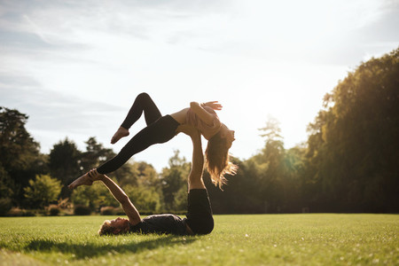 Fit couple doing acrobatic yoga exercise in park
