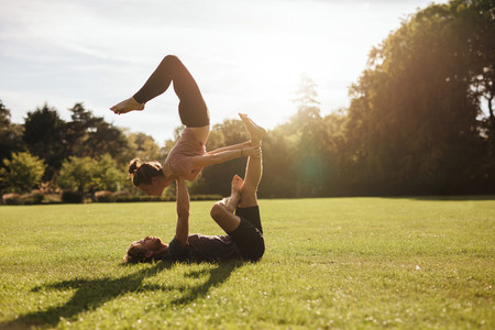 Strong young couple doing acroyoga workout