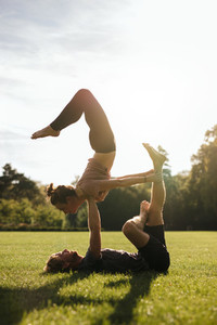 Young couple doing acrobatic pair yoga