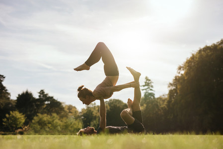 Healthy young couple doing acro yoga outdoors