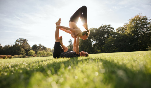 Young couple doing acrobatic yoga