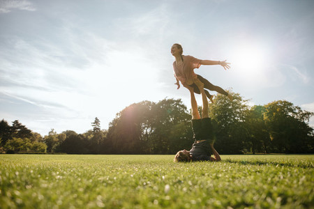 Healthy young couple doing acrobatic yoga at park