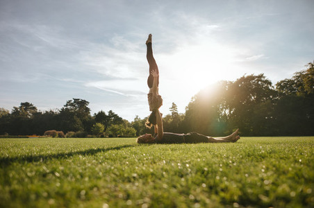 Couple doing pair yoga in park
