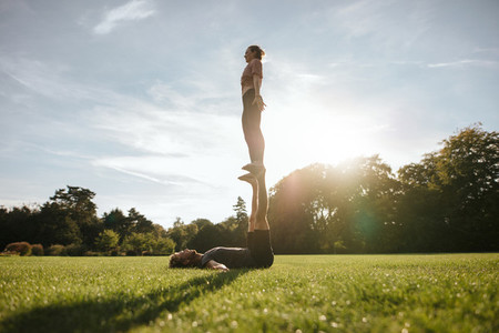 Fit couple doing acrobatic yoga exercise