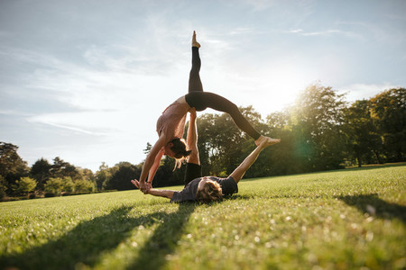 Fit couple doing acrobatic exercise in park